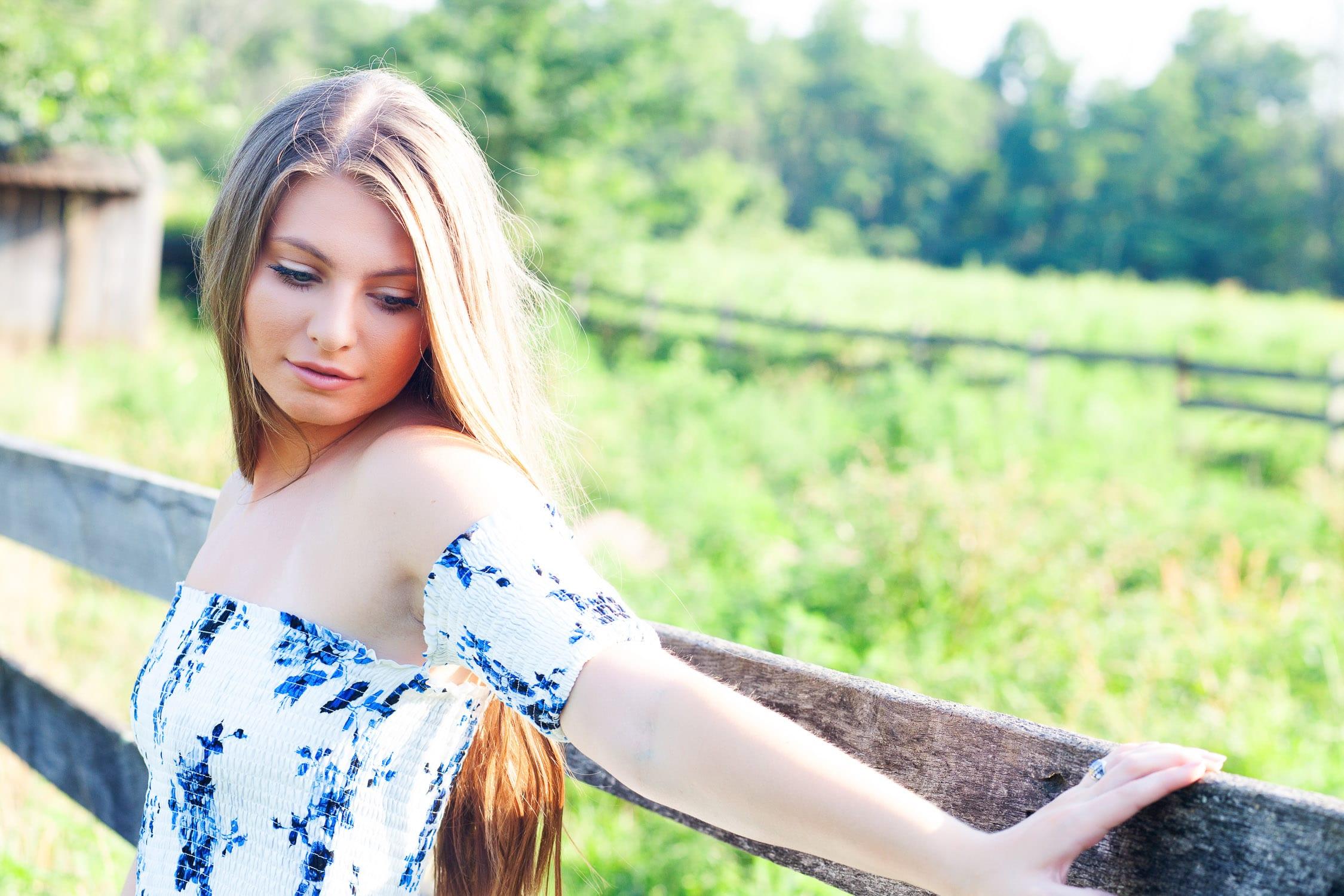 louisville senior girl at blackacre farm leaning against wooden fence