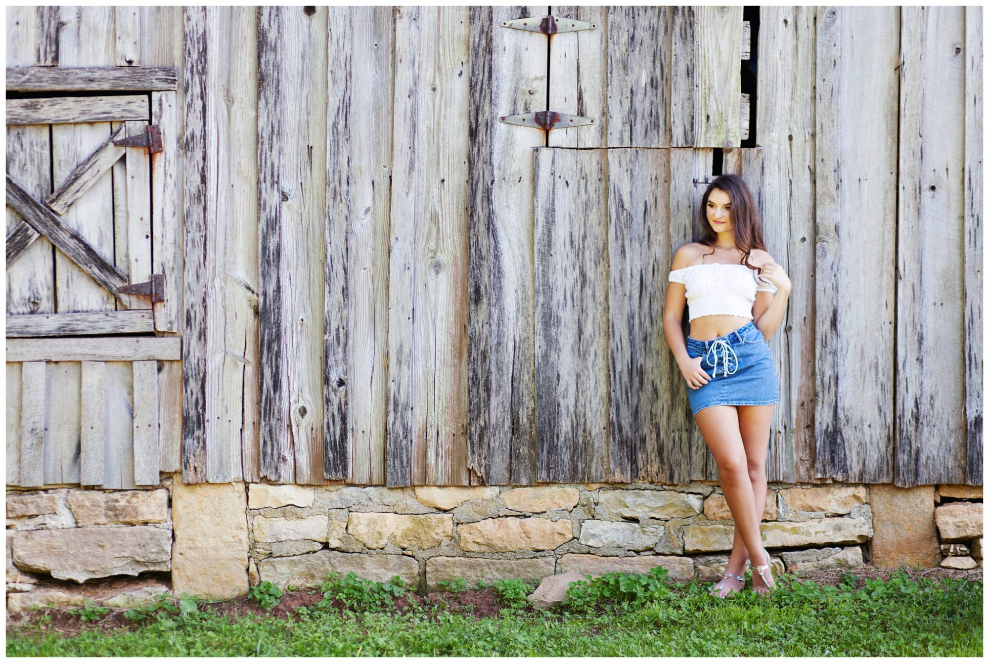 High school senior standing against old wooden barn
