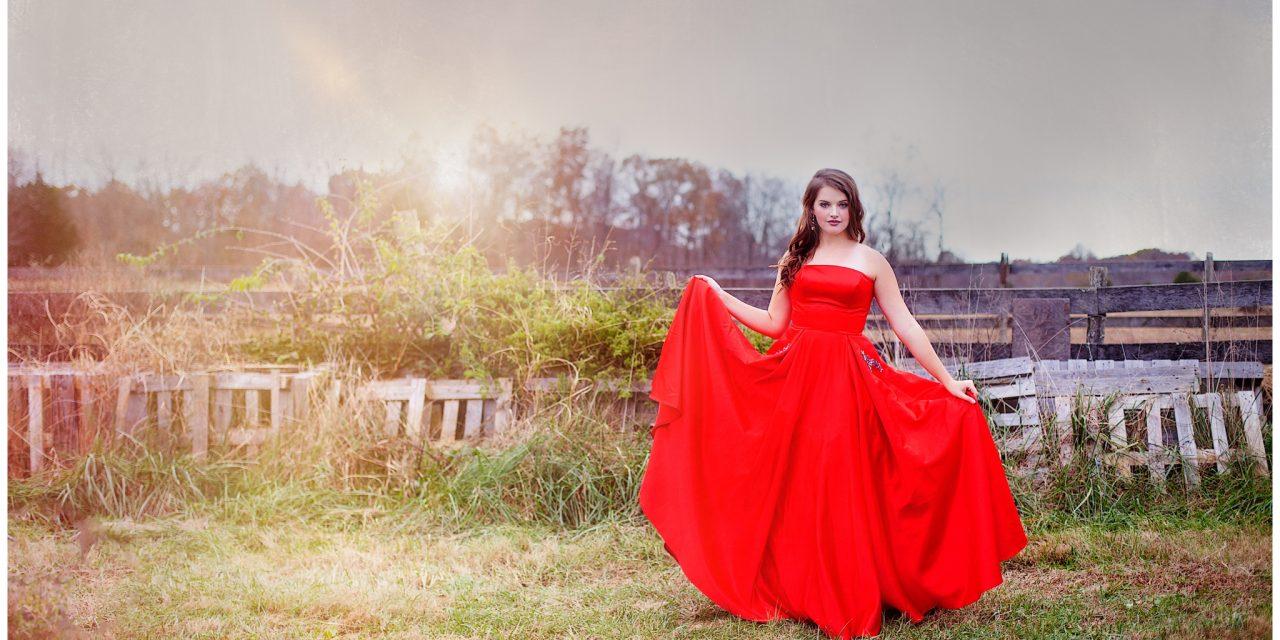 Girl in red prom dress standing in open field