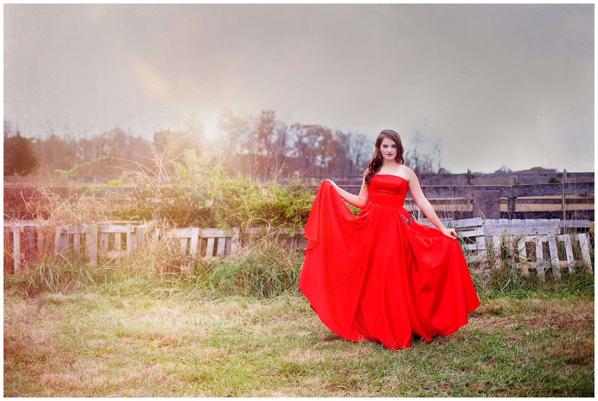 Girl in red prom dress standing in open field